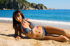 Beautiful young woman lying on sand Stock Photography