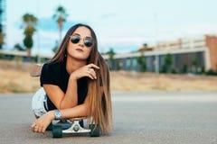 Beautiful young woman lying on skateboard
