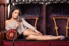 Beautiful young woman lying and smoking hookah. Stock Image