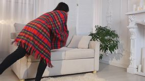 Beautiful young woman lying on sofa under blanket at home stock video footage
