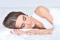 Beautiful young woman lying on soft  bed royalty free stock photography