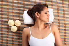 Beautiful young woman lying in spa head on towel Royalty Free Stock Photos