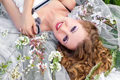 Beautiful young woman lying in spring blossom Stock Photography