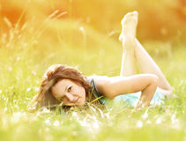 Beautiful young woman lying on summer field on a sunny day Royalty Free Stock Images