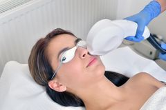 Beautiful young woman lying on a table with protect glasses on e. Yes getting a laser skin treatment Royalty Free Stock Photo