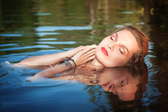 Beautiful young woman lying in the water Royalty Free Stock Image