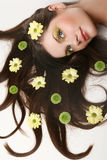 Beautiful young woman lying on white background. Beautiful young woman lying on isolated white background with flowing hair and flowers Royalty Free Stock Photo