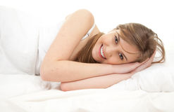 Beautiful young woman lying in white bedding Royalty Free Stock Photography