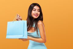 Shopping Festival . Happy asian woman at shopping holding bag and phone isolated on blue background on Black Friday Stock Photography