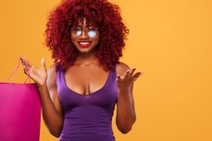 Afro american woman at shopping holding pink bag isolated on orange background on black friday holiday. Copy space for Royalty Free Stock Photos