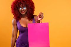Afro american woman at shopping holding pink bag  on orange background on black friday holiday. Copy space for Stock Photos