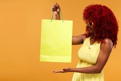 Afro american woman at shopping show on yellow bag isolated on orange background on black friday holiday. Copy space for Stock Photography