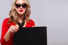 Blonde woman at shopping holding dark bag isolated on gray background on black friday holiday. Copy space for sale ads. Beautiful young woman make shopping in Royalty Free Stock Photos