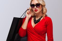 Blonde woman at shopping holding dark bag isolated on gray background on black friday holiday. Copy space for sale ads. Royalty Free Stock Image