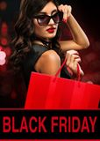 Black friday sale concept. Shopping woman in sunglasses holding bag on background with bokeh lights in holiday royalty free stock image