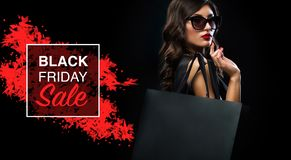 Black friday sale concept. Shopping woman holding grey bag isolated on dark background in holiday stock photography