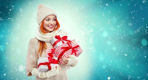Shopping woman holding gift boxes on winter background with snow in black friday, Christmas and New Year holidays. Sale. Beautiful young woman make shopping in royalty free stock image