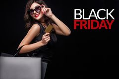 Shopping woman holding grey bag on dark background in black friday holiday. Beautiful young woman make shopping in black friday holiday. Girl with black bag on royalty free stock photography