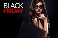 Shopping woman holding grey bag on dark background in black friday holiday Royalty Free Stock Photos