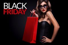 Shopping woman holding red bag on dark background in black friday holiday. Beautiful young woman make shopping in black friday holiday. Girl with red bag on dark Royalty Free Stock Images