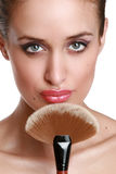 Beautiful young woman with a make-up brush. Royalty Free Stock Photography