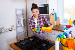 Beautiful young woman makes cleaning the house. Girl cleaning ki Royalty Free Stock Photography