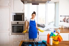 Beautiful young woman makes cleaning the house. Girl cleaning kitchen. Set. stock photos