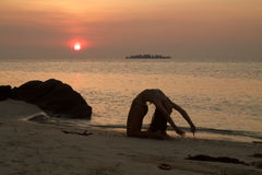 Beautiful young woman makes gymnastic exercises on the beach. On sunset Stock Photography