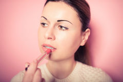 Beautiful young woman makes up lips Stock Photography