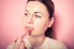 Beautiful young woman makes up lips. Fashion Stock Photography