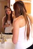 Beautiful young woman during makeups Stock Images