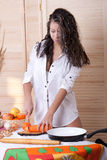 Beautiful young woman making breakfast in kitchen Royalty Free Stock Images