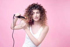 Beautiful young woman making curls with curling iron. royalty free stock photos