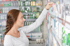 Beautiful young woman making decision. In drugstore Stock Photos