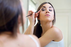 Beautiful young woman making make-up near mirror. Royalty Free Stock Images