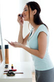 Beautiful young woman making make-up near mirror. Stock Image