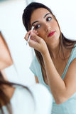 Beautiful young woman making make-up near mirror. Stock Images
