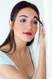 Beautiful young woman making make-up near mirror. Royalty Free Stock Photo