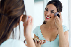Beautiful young woman making make-up near mirror. Stock Photo