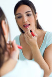 Beautiful young woman making make-up near mirror. Stock Photography