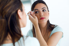 Beautiful young woman making make-up near mirror. Royalty Free Stock Photos