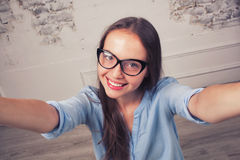 Beautiful young woman making self-portrait on Royalty Free Stock Photo