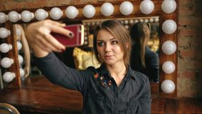 Beautiful young woman making selfie portrait on a smartphone in dressing room indoors Royalty Free Stock Images