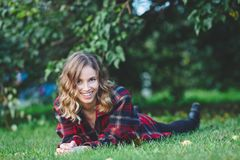 Beautiful young woman in a male flannel shirt lying on green grass. Outdoor portrait in city park Royalty Free Stock Images