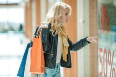 Shocked woman at sale. Beautiful young woman with mall bags looking shocked and surprised while shopping at sale Stock Photography
