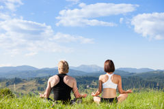 Beautiful young woman and man doing yoga exercise. Beautiful young women and men doing yoga exercise at the summer meadow Royalty Free Stock Photos