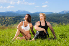 Beautiful young woman and man doing yoga exercise. Beautiful young women and men doing yoga exercise at the summer meadow stock photos