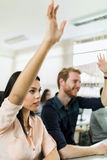 Beautiful young woman and a man raising hands in classroom Royalty Free Stock Images