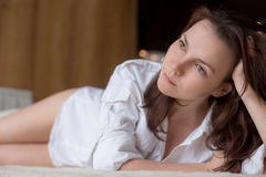 Beautiful young woman in man's shirt laying on bed.  Royalty Free Stock Images