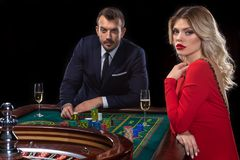 A beautiful young woman and a man are sitting at a roulette table. Casino. Stock Image